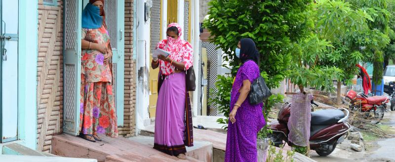 Anganwadi workers wearing mask interacts with a woman during a door-to-door survey to check the spread of novel coronavirus, on the outskirts of Beawar.