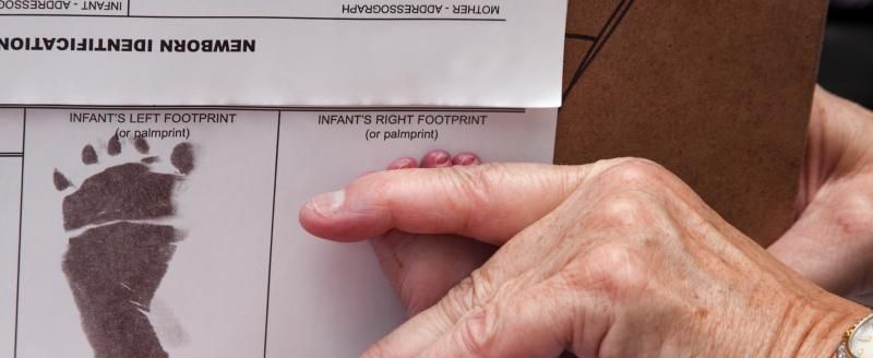 Doctor recording a newborns foot prints on the birth certificate.